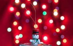 Pequeño juguete del muñeco de nieve en frente del bokeh rojo Imagen de archivo libre de regalías