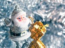Pequeño juguete Santa Claus con los regalos en un fondo de plata brillante brillante Fotografía de archivo libre de regalías