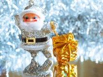 Pequeño juguete Santa Claus con los regalos en un fondo de plata brillante brillante Imágenes de archivo libres de regalías