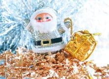 Pequeño juguete Santa Claus con los regalos en un fondo de plata brillante brillante Fotos de archivo