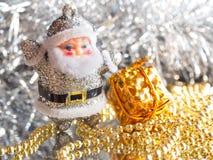 Pequeño juguete Santa Claus con los regalos en un fondo de plata brillante brillante entonado Fotografía de archivo libre de regalías