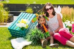 Pequeño kazakh adorable, muchacha asiática del niño con la madre con la zanahoria en fondo de la naturaleza del verde del verano imagen de archivo
