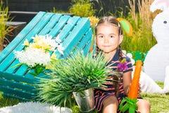 Pequeño kazakh adorable, muchacha asiática del niño con la zanahoria en fondo de la naturaleza del verde del verano imagen de archivo