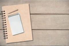 Pequeño lápiz en el libro vacío en la tabla de madera, fondo de la visión superior, espacio de la copia, falso para arriba fotografía de archivo libre de regalías