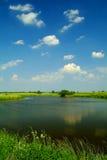 Pequeño lago bajo un cielo azul Imagenes de archivo