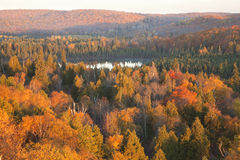 Pequeño lago entre las colinas y los árboles con color de la caída en Minnesota septentrional Fotos de archivo