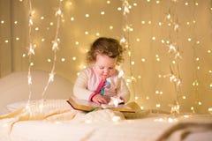 Pequeño libro de lectura lindo de la niña pequeña en sitio oscuro con las luces de la Navidad Imágenes de archivo libres de regalías