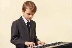 Pequeño músico del principiante en el traje que juega el sintetizador Imagen de archivo