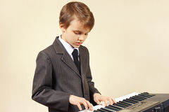 Pequeño músico en el traje que juega el piano electrónico Imágenes de archivo libres de regalías