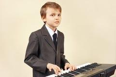 Pequeño músico en el traje que juega el piano digital Fotos de archivo