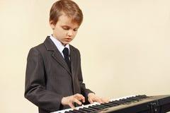 Pequeño músico en el traje que juega el sintetizador electrónico Fotos de archivo