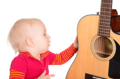Pequeño músico lindo que toca la guitarra aislada en el fondo blanco Fotos de archivo