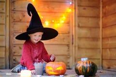 Pequeño mago lindo con la vara y las Jack-o-linternas mágicas Foto de archivo
