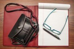 Pequeño monedero y cuaderno y cuero rojo y negro de la endecha plana de los vidrios de la pluma y de lectura - con los vidrios de Fotografía de archivo