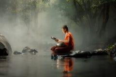 Pequeño monje de Tailandia que se sienta en The Creek o el río en bosque en Imágenes de archivo libres de regalías