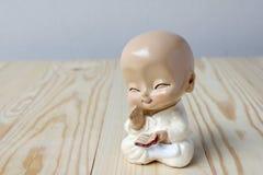 Pequeño monje que ruega, neófito de la estatua en fondo de madera de pino imágenes de archivo libres de regalías