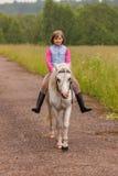 Pequeño montar a caballo del niño en un caballo blanco en el camino al aire libre Imagen de archivo libre de regalías