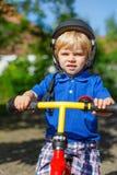 Pequeño montar a caballo del niño pequeño en su bycicle en verano fotos de archivo