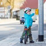 Pequeño montar a caballo preescolar del muchacho del niño con su primera bici verde Fotos de archivo libres de regalías