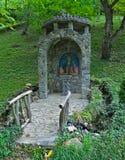 Pequeño monumento cristiano de piedra adornado en parque Fotos de archivo