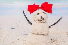 Pequeño muñeco de nieve arenoso con el arco en el Caribe blanco Imagen de archivo