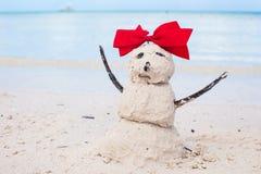 Pequeño muñeco de nieve arenoso con el arco en el Caribe blanco Imágenes de archivo libres de regalías