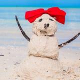 Pequeño muñeco de nieve arenoso con el arco en el Caribe blanco Fotografía de archivo libre de regalías