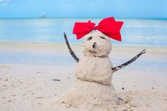 Pequeño muñeco de nieve arenoso con el arco en un Caribe arenoso Imagen de archivo libre de regalías