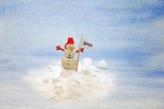 Pequeño muñeco de nieve en la nieve con una bandera Imágenes de archivo libres de regalías