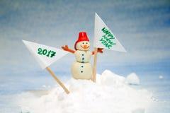 Pequeño muñeco de nieve en la nieve con una bandera Imagen de archivo
