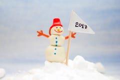 Pequeño muñeco de nieve en la nieve con una bandera Imagen de archivo libre de regalías