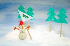 Pequeño muñeco de nieve en la nieve con una bandera Foto de archivo libre de regalías