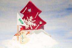 Pequeño muñeco de nieve en la nieve con una bandera Imagenes de archivo