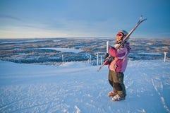 Pequeño muchacha-esquiador en la colina que mira la salida del sol Fotografía de archivo