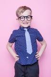Pequeño muchacho adorable en lazo y vidrios Escuela pre-entrenamiento Moda Retrato del estudio sobre fondo rosado imagen de archivo libre de regalías