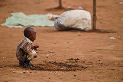 Pequeño muchacho africano que se pone en cuclillas Fotografía de archivo libre de regalías