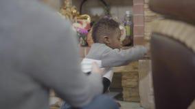 Pequeño muchacho afroamericano lindo del niño que toma los juguetes del paquete y que muestra a la huésped en el fondo de la c almacen de video