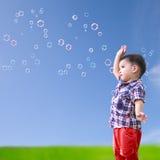 Pequeño muchacho asiático del bebé que se opone al cielo azul con la burbuja de jabón Imágenes de archivo libres de regalías