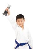 Pequeño muchacho asiático del karate que sostiene la taza en el kimono blanco Imágenes de archivo libres de regalías