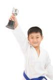 Pequeño muchacho asiático del karate que sostiene la taza en el kimono blanco Fotografía de archivo libre de regalías