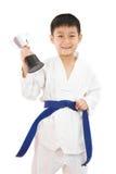 Pequeño muchacho asiático del karate que sostiene la taza en el kimono blanco Fotos de archivo