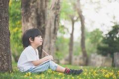Pequeño muchacho asiático que se sienta debajo del árbol y que dibuja en cuaderno imagen de archivo
