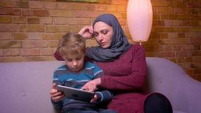 Pequeño muchacho atento que juega al juego en la tableta y su madre musulmán en hijab observando su actividad en casa metrajes