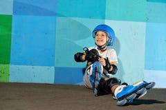 Pequeño muchacho atlético lindo en el rodillo que se sienta contra la pared azul de la pintada Imagen de archivo libre de regalías