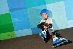 Pequeño muchacho atlético lindo en el rodillo que se sienta contra la pared azul de la pintada Imagenes de archivo