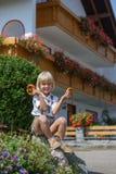 Pequeño muchacho bávaro feliz que sostiene un pretzel en manos en lejos Fotos de archivo