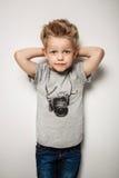 Pequeño muchacho bonito que presenta en el estudio como modelo de moda Fotos de archivo