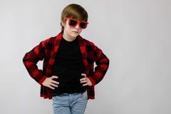 Pequeño muchacho caucásico confiado lindo en camisa a cuadros en las gafas de sol rojas que engañan en fondo gris Imagen de archivo libre de regalías