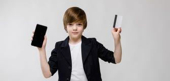 Pequeño muchacho caucásico confiado lindo en chaqueta negra con el teléfono móvil y tarjeta de crédito en fondo gris Imagenes de archivo