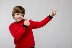 Pequeño muchacho caucásico confiado lindo en el suéter rojo que muestra en área en blanco en fondo gris Fotos de archivo